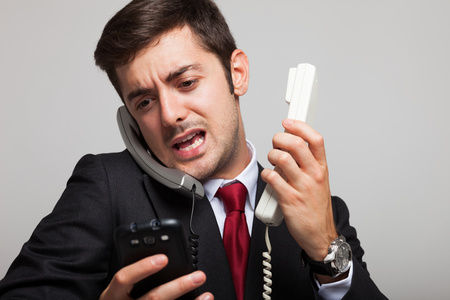 Photo pour Stressed businessman talking on many phones at once - image libre de droit