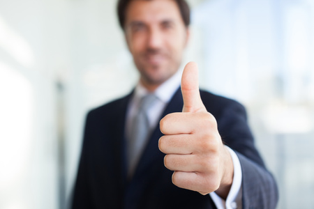 Foto de Portrait of a smiling businessman giving thumbs up - Imagen libre de derechos