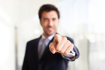 Smiling businessman pointing his finger at you