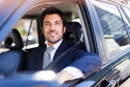 Foto de Portrait of an handsome smiling business man driving his car - Imagen libre de derechos