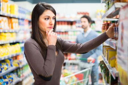 Photo pour Woman shopping in a supermarket - image libre de droit
