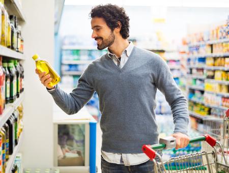 Foto für Man taking a bottle of oil from a shelf in a supermarket - Lizenzfreies Bild