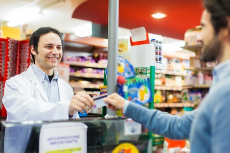 Photo pour Customer using a credit card to pay in a supermarket - image libre de droit