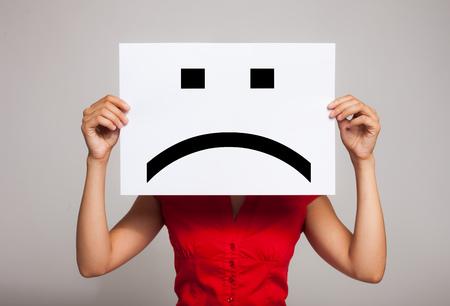 Photo pour Woman holding a sad face emoticon - image libre de droit