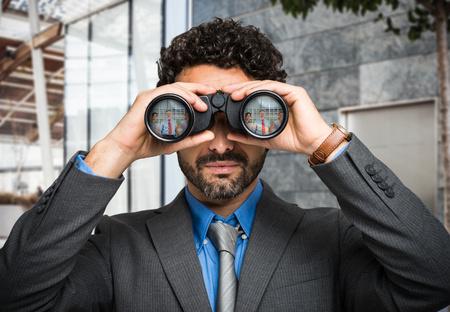 Photo pour Portrait of a businessman using binoculars, people portraits reflected in the lens - image libre de droit