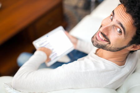 Photo for Man using a tablet while relaxing on the couch - Royalty Free Image
