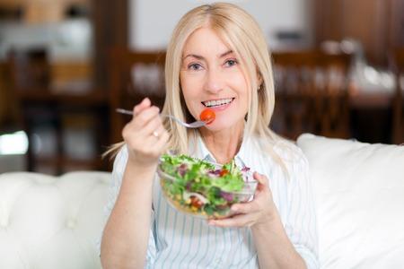 Photo pour Mature woman eating a healthy salad on her sofa - image libre de droit