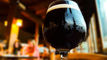 Photo for Glass of fresh dark beer on rustic pub background - Royalty Free Image