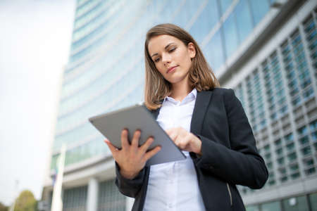 Photo pour Portrait of a young woman using a tablet out of her office - image libre de droit
