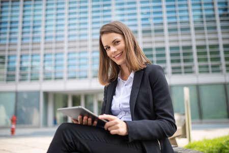 Photo pour Smiling businesswoman using a digital tablet outdoor sitting on a bench - image libre de droit
