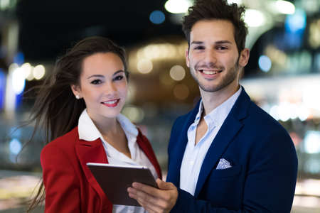 Photo pour Couple of business people using a tablet outdoor - image libre de droit