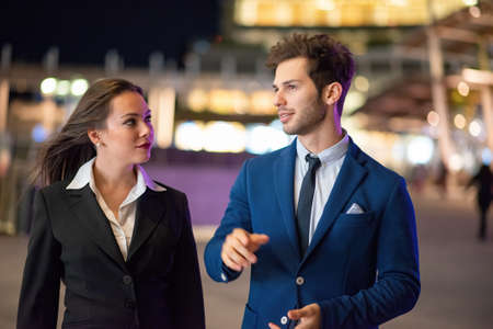 Photo pour Business partners discussing together late in the evening in a modern city setting - image libre de droit