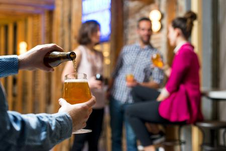 Photo pour Serving a beer while friends drink and smile - image libre de droit