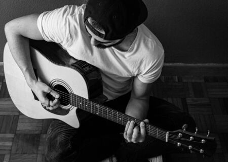 Young man with a cap and white t-shirt focused playing an acoustic guitar sit on the floor. Selective focus. Grain. b&w.
