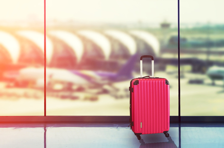 Photo pour Pink suitcases in airport departure lounge, airplane in background, summer vacation concept, traveler suitcases in airport terminal waiting area. - image libre de droit