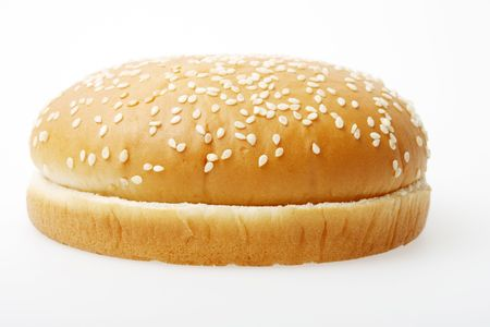 A hamburger bun on a light grey surface.