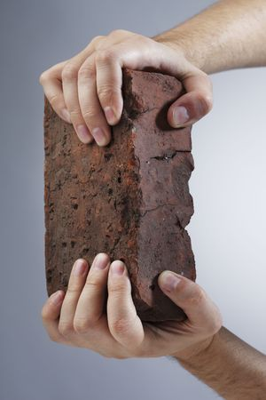 Hands holding an old brick