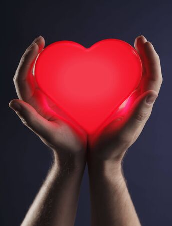 Photo pour Man holding a red glowing heart in his hands. - image libre de droit