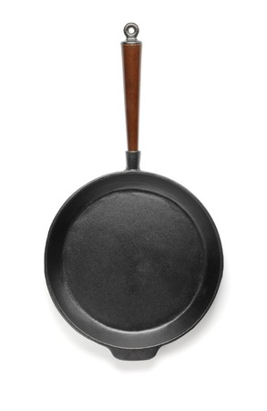 Old fashioned cast iron frying pan isolated on white with natural shadows.