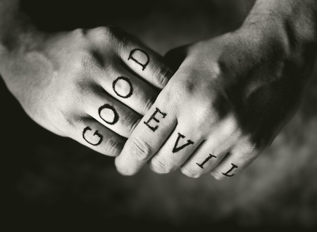 Man with Good and Evil (fake) tattoos on his fingers.
