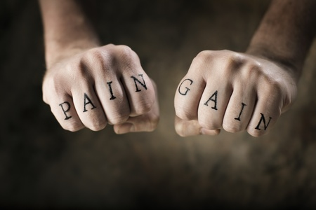 Man with fake tattoos Pain and Gain on his hands, referring to the exercise motto No Pain, No Gain.