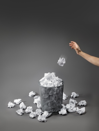 Hand throwing a crumpled paper into a waste paper basket.