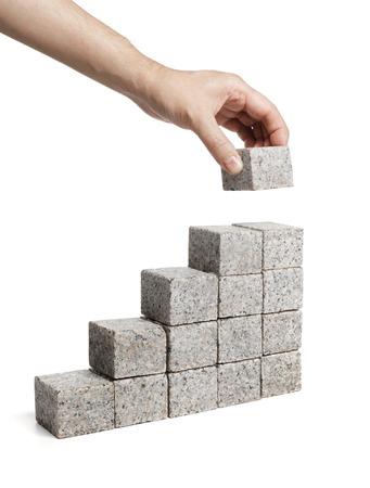 Man stacking blocks made of granite rock.