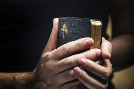 Photo for Man holding an old small black bible in his hands. Short depth of field, the sharpness is in the cross. - Royalty Free Image