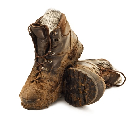 Pair of dirty brown walking boots caked in mud isolated on a white backgound