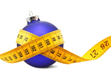 Tape measure around a bauble concept symbolizing Christmas weight gain from eating too much food