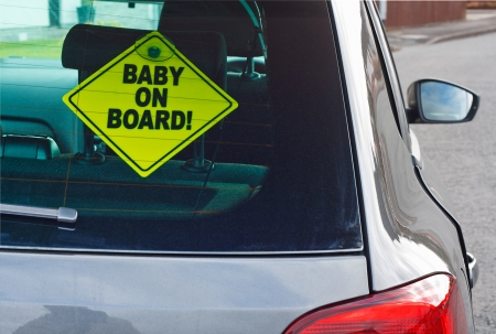 Baby on board warning sign in the back window of a car to advise cars behind of the presence of a toddler