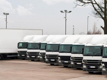 Foto de Company fleet of commercial lorries parked in a row ready for cargo distribution - Imagen libre de derechos