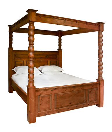 Traditional wooden Four Poster Bed isolated against a white background