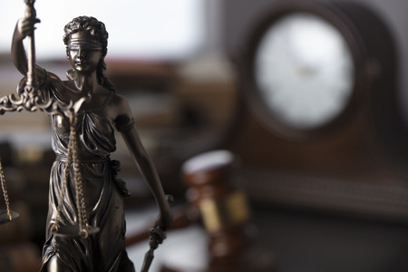 Judge's gavel and Themis statue – symbols of law and justice.