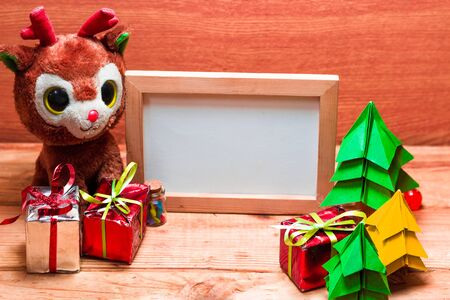 Blank whiteboard for your text on wooden background with Christmas tree, gift box and Teddy reindeer decoration image for Christmas holiday concept.