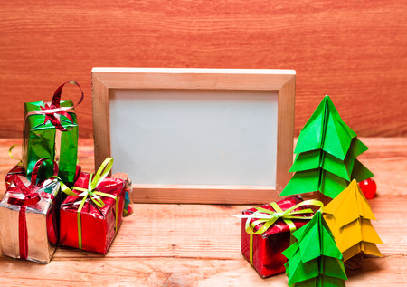 Blank whiteboard for your text on wooden background with Christmas tree, gift box and Christmas ball decoration image for Christmas holiday concept.