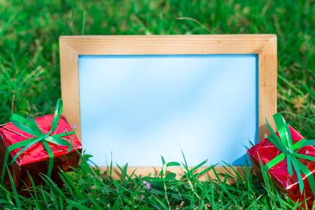 Blank whiteboard for your text on lawn  background with christmas gift box for Christmas holiday concept, on sunlight day.