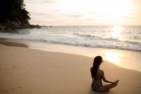 Photo pour beautiful girl yoga coach sitting near the sea and meditating looking at the setting sun in - image libre de droit
