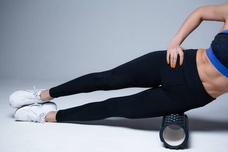 Photo pour Close up of legs. Pilates trainer kneads the fascia of lateral muscles of the thigh with a massage roller before starting exercise - image libre de droit