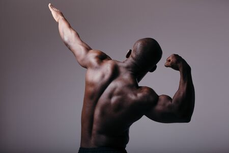 Photo for Back view. Men's inflated back. African man shows muscles and raises one arm up - Royalty Free Image