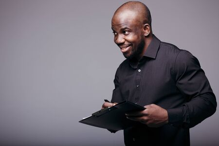 Dark-skinned Ethiopian in a black shirt holds a black tablet with papers and looks attractively at a client on a gray background