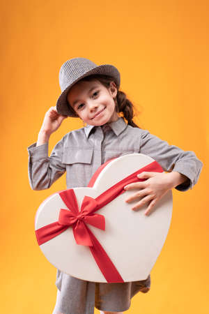 Photo pour A girl touches the hat on her head and holds in her hand a wrapped gift with a bow in the shape of a large heart - image libre de droit