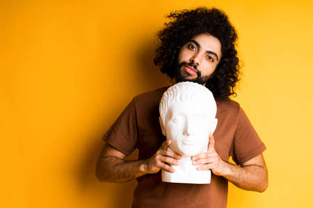 Photo pour Handsome Egyptian with a beard standing on a yellow background and holding a head sculpture tilting his head to the side - image libre de droit