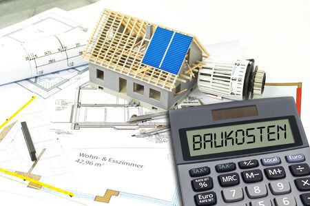 Photo pour Construction or building plan with bricks and calculator showing the german word for building costs - baukosten - image libre de droit