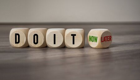 Photo pour Cubes and dice with the words Do It now and later on wooden background - image libre de droit