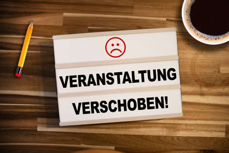 Photo pour Lightbox or light box with the german words for This event is postponed - Event appointment postponed on wooden table background - image libre de droit