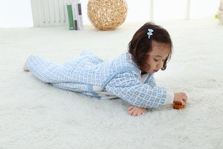 The little girl in a blue dress near a window. Portrait of the little girl. Dress of the princess