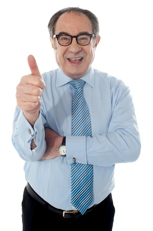 Matured businessman gesturing thumbs-up sign at you isolated on white