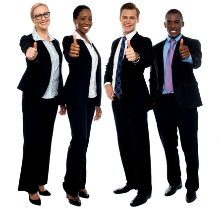 Full length portrait of successful corporate team gesturing thumbs up