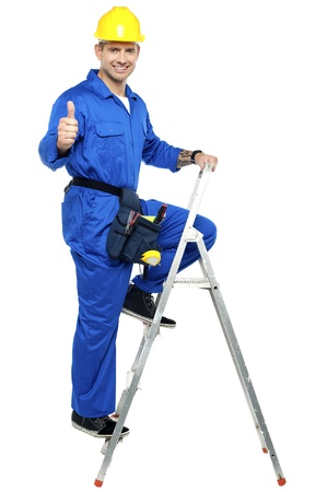 Industrial contractor gesturing thumbs up while climbing on the ladder